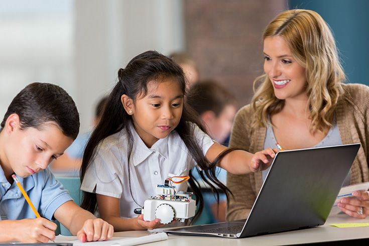 Teacher, girl with robot in front of a computer, and a boy writing in a notebook
