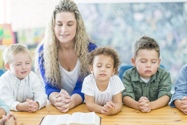 teacher and young children praying